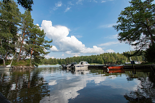 Askersund Sweden July 2020\nfew boats in the water, fresh water lake and blue cloudy sky