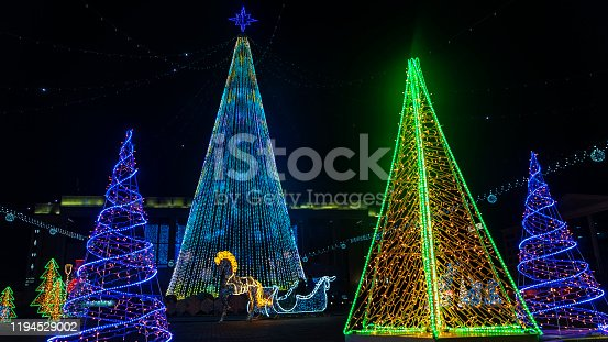 865140324 istock photo Few christmas trees in the holiday illumination. Central square in Minsk. 1194529002