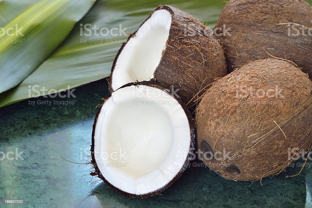 Few coconuts on green marble slab royalty-free stock photo