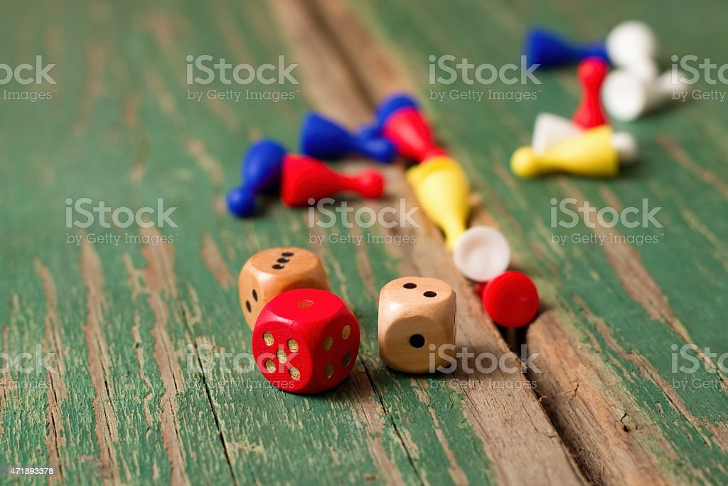 Few dices and color figurines on green wooden board stock photo