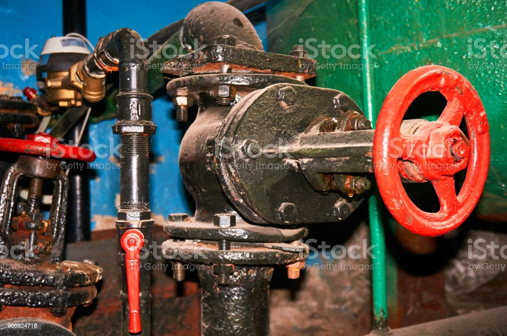 A few old painted black with red valves on the cold water pipeline. stock photo