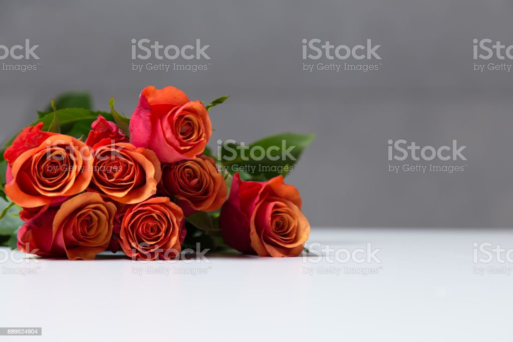 Few orange and red rose flowers on white table surface. Bouquet on a blur abstract background with copy space. stock photo