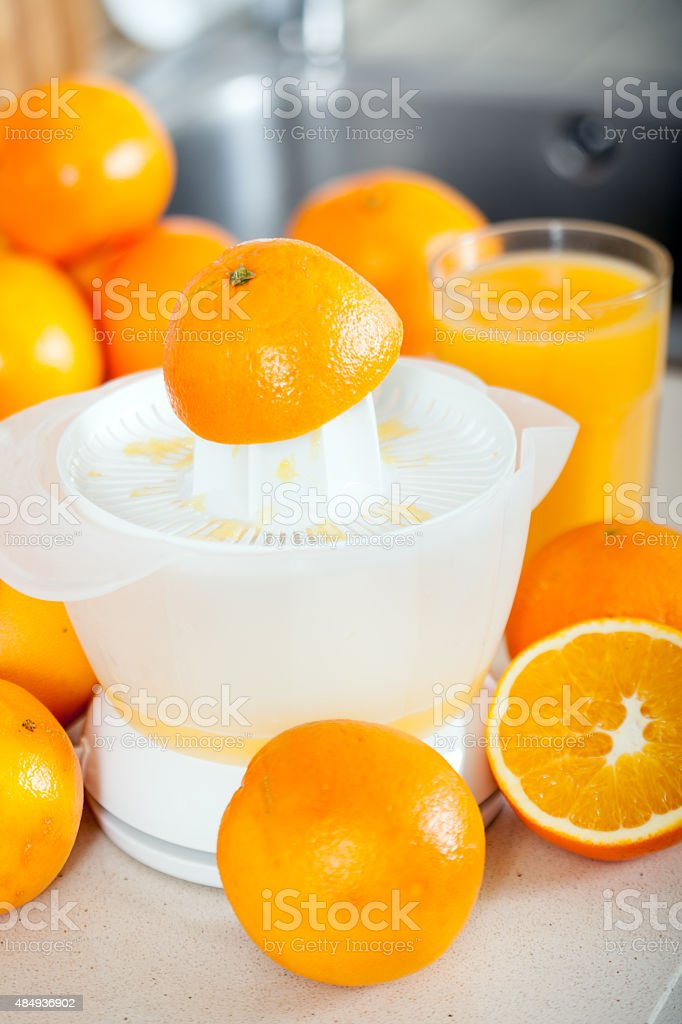 few oranges near the hand juicer stock photo