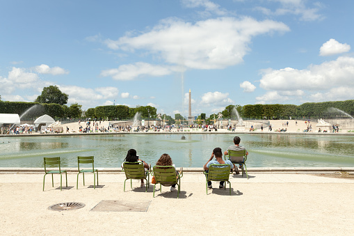 Few people among other tourists and Parisians rest in Tuileries garden near Louvre museum. Tuileries garden became a public park after the French Revolution.