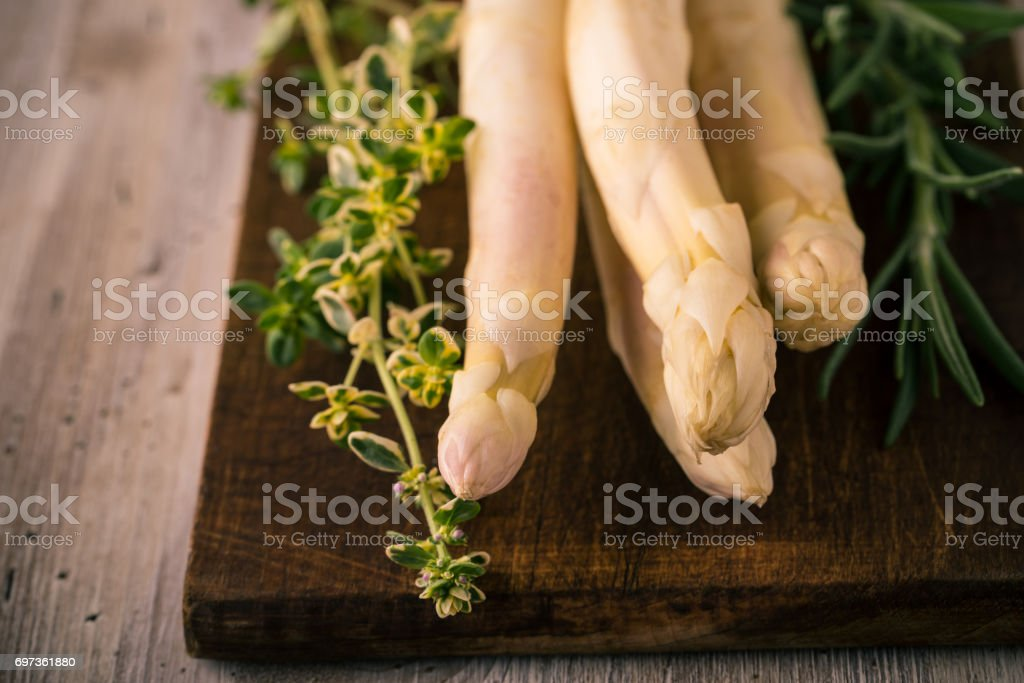 Few pieces of asparagus on chopping board with green herbs stock photo