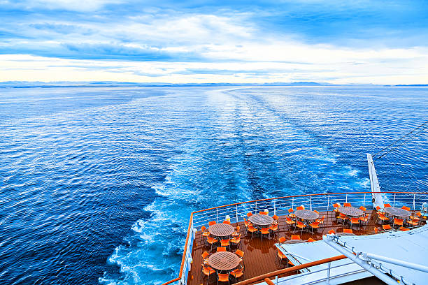 few round tables with chairs on deck - cruise stockfoto's en -beelden
