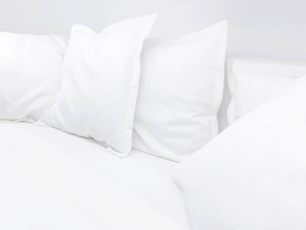 Few white pillows on bed. Clear white bed linen for restful sleep. stock photo