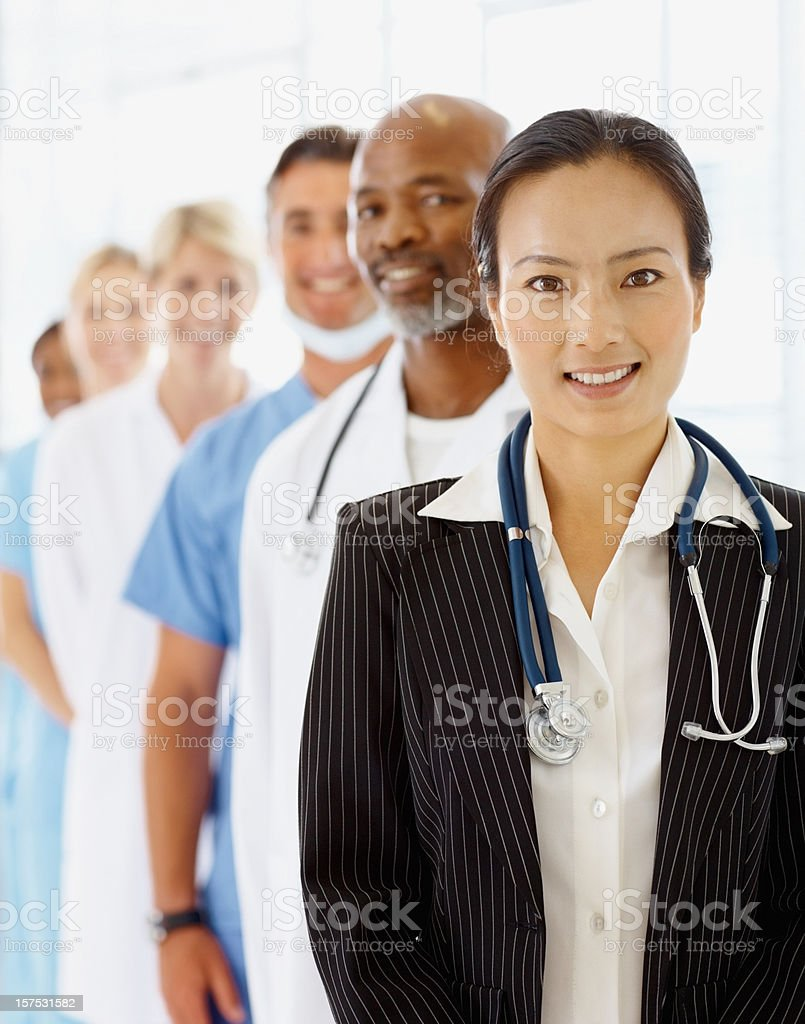 Ffemale doctor smiling with colleagues at the back royalty-free stock photo