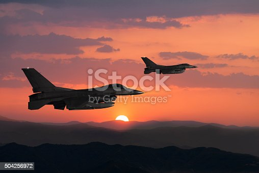 Two Fıghter Jet flying over the mountains at sunset