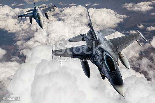 Two Fıghter Jet fighter jets flying in formation over the clouds.