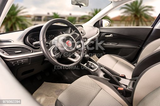 Novi Sad ,Serbia - Jun 15, 2018: White and black interior on a Fiat 500 compact retro styled hatchback car. The car is fitted with a white steering wheel, old fashioned dials and an information display on the dashboard.