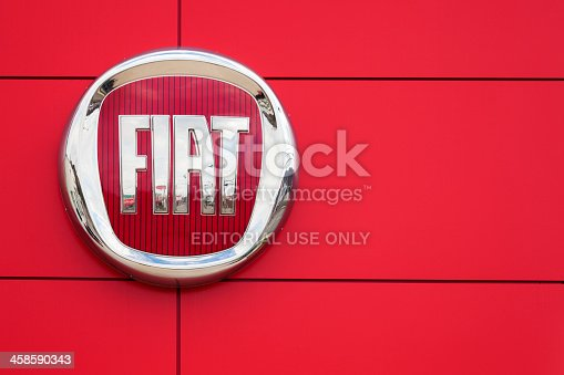 Saint John, New Brunswick, Canada - April 29, 2012: Fiat Logo and sign on a wall at a car dealership.  Reflection of dealership slightly visible in Fiat sign.  Fiat recently returned to the North American market with the popular Fiat 500 after a 27 year absence.