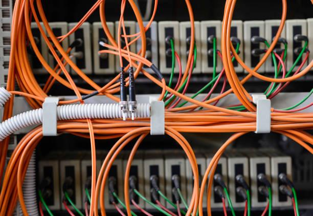 ネットワーク デバイスに接続された光ファイバ コネクタと多数の光ケーブル ストックフォト