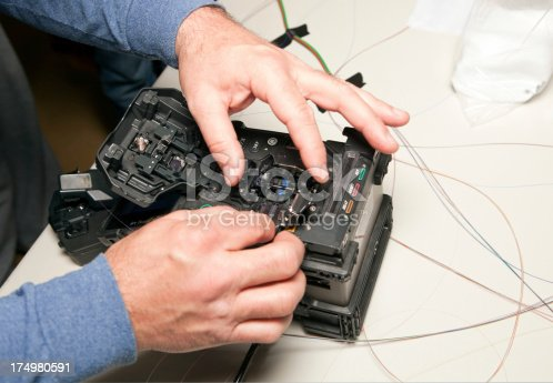 A hand is placing a strand of fiber optic cable into a fusion splicing system. The machine automatically aligns and creates a splice. This is current telecommunications technology and this cable is the same as used in the industry. The white surface is a plastic banquet table with some texture and debris. The equipment has some dust and signs of wear.