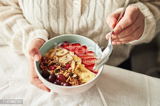 Cropped shot of a woman having a bowl of granola and fruit at home