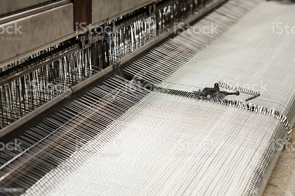 Close-up view of a working fibreglass weave machine in a factory