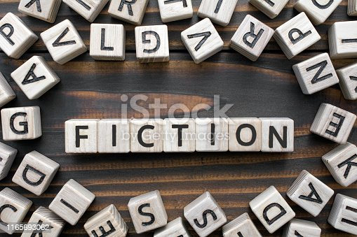 fiction - word from wooden blocks with letters, Literary Genres concept, random letters around, top view on wooden background