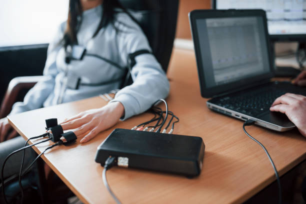 Fidelity verification. Girl passes lie detector in the office. Asking questions. Polygraph test stock photo