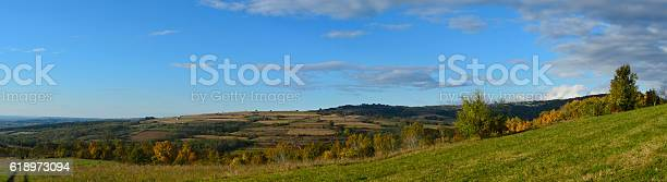 Photo of field and hills with cloudy sky