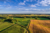 An aerial drone photo over the fields and dirt road lanes in the fields during the golden light of the morning.