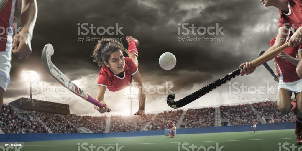 Field Hockey Player Diving to Hit Ball stock photo