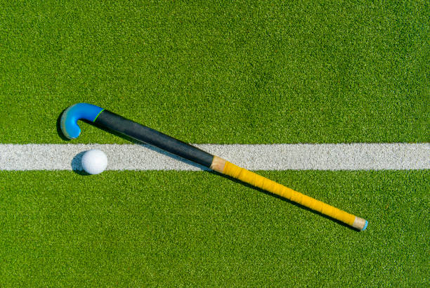 field hockey stick and ball on green grass - hockey stick stock pictures, royalty-free photos & images