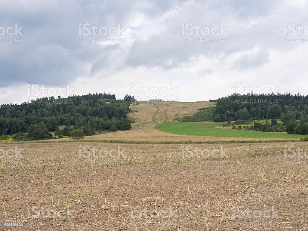 Field In Front Of A Woody Hill With A House royalty-free stock photo