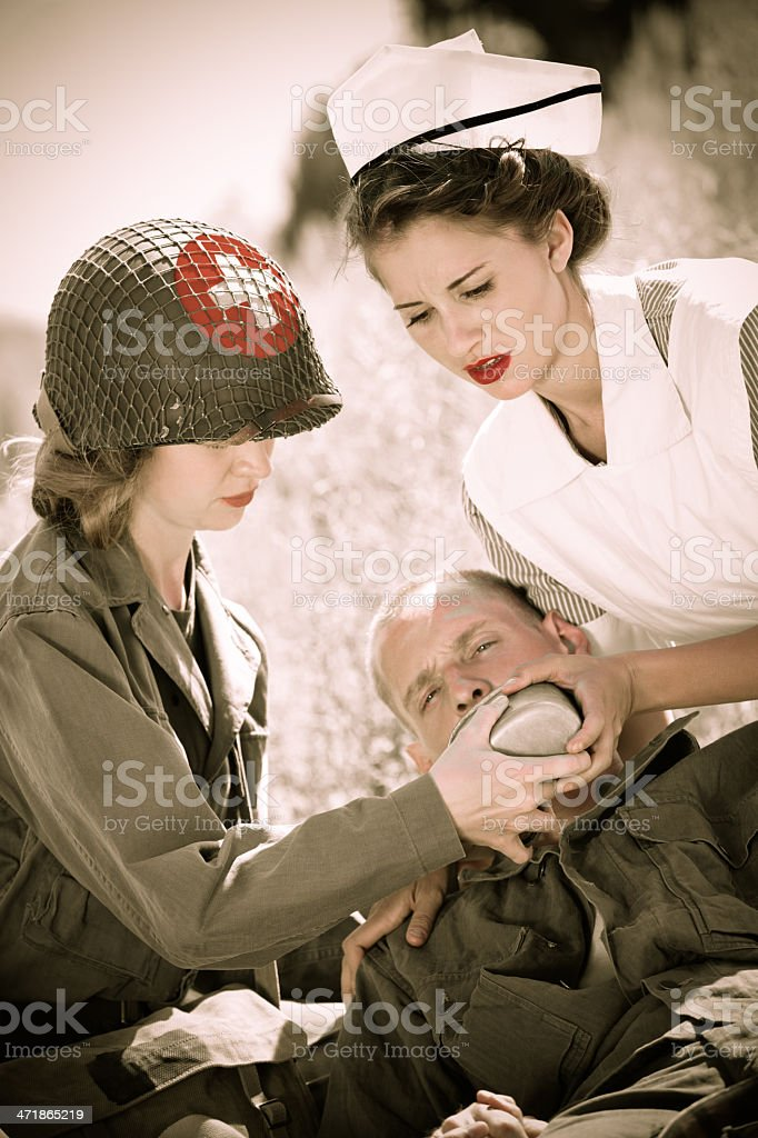 WW2 Field medic & nurse helping wounded soldier stock photo