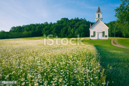 istock field of daisy wildflowers and old country church 165935619