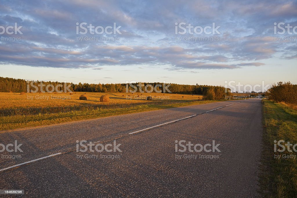 field of haystacks at sunset and road royalty-free stock photo