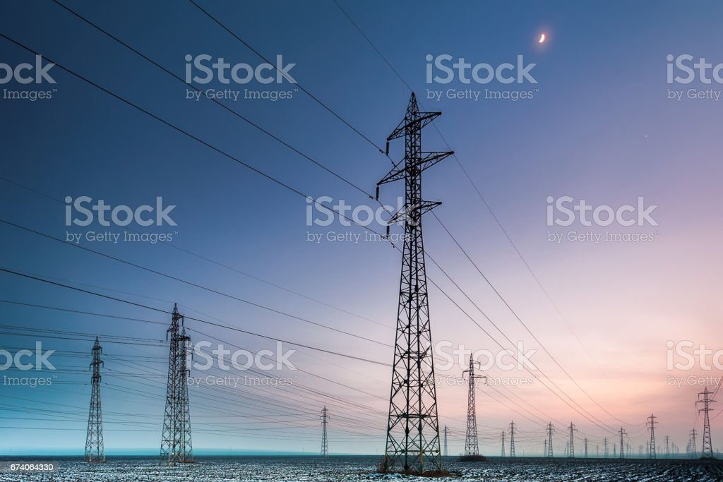 Field of power pylons at dusk stock photo