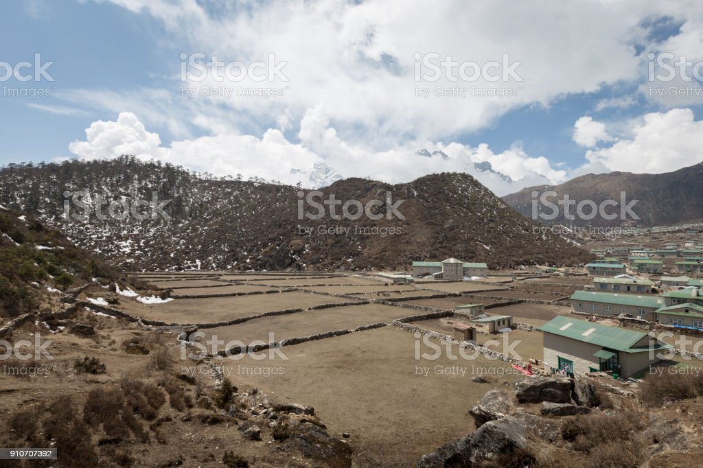 Field plantation at Dingboche, Nepal on overcast day with some buildings stock photo