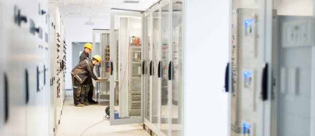Field service crew testing electronics or inspecting electrical installation system Field service crew testing electronics or inspecting electrical installation system. Bay control unit. Medium voltage switchgear coupling device stock pictures, royalty-free photos & images