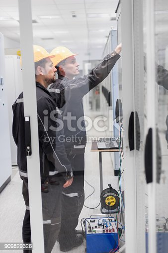 istock Field service crew testing electronics or inspecting electrical installation system 909829326