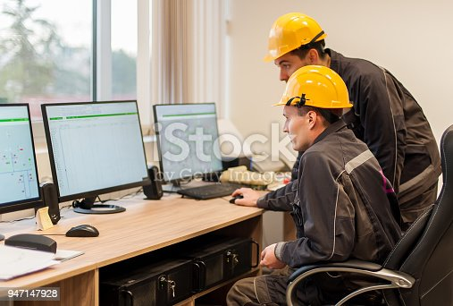 istock Field service engineers inspect relay protection system with laptop computer 947147928
