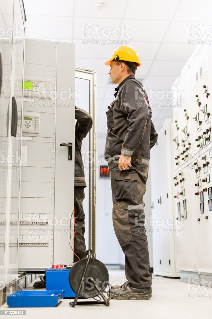Field service engineers inspect system with relay test set equipment stock photo
