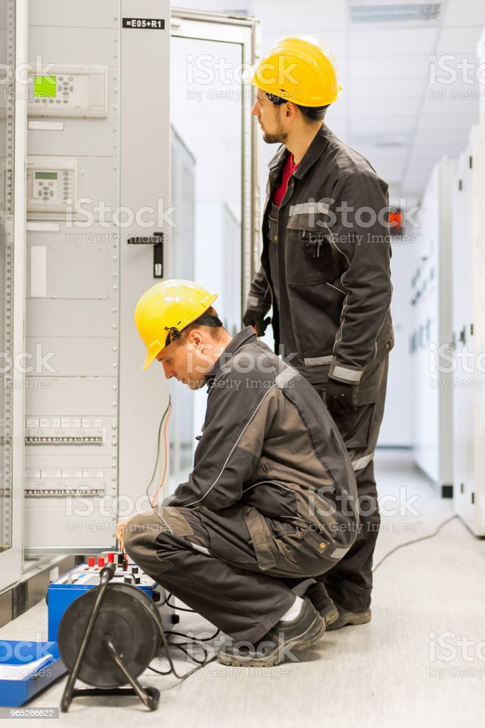 Field service engineers inspect system with relay test set equipment royalty-free stock photo