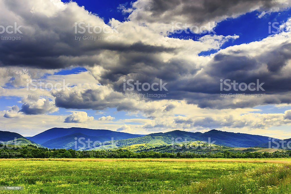 field  under clouds royalty-free stock photo