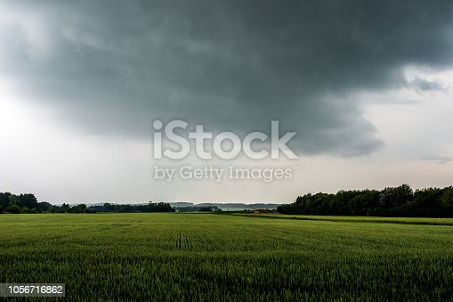 istock Field under dark clouds shortly before a thunderstorm 1056716862