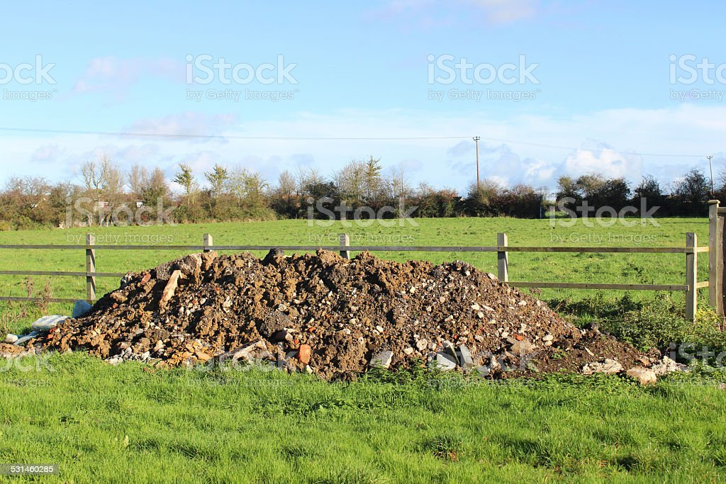 Field with pile of rubble soil mound / rubbish-dump heap / fly-tipping stock photo