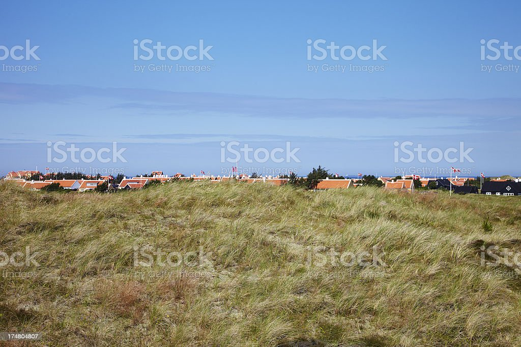 Field with town houses against blue sky royalty-free stock photo