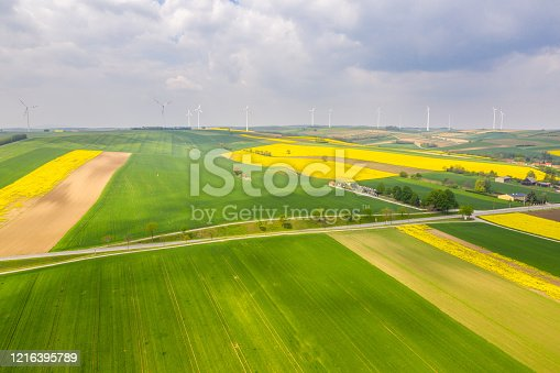 Idyllic countryside landscape with the view of agricultural fields and wind turbines in the background.