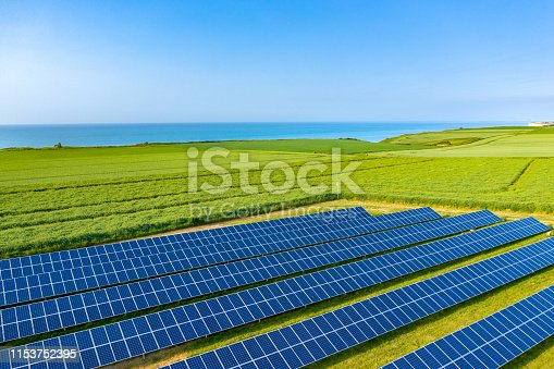 Cette photo a été prise en France, au nord de la Normandie, à proximité de Saint-Valery-en-Caux. On y voit un champ de panneaux solaires au milieu de champs de colza et de lin au bord de la mer.