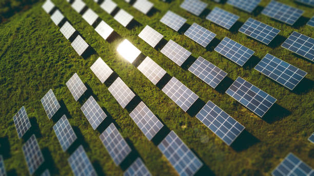 Fields of solar panels on the green hills in spring stock photo