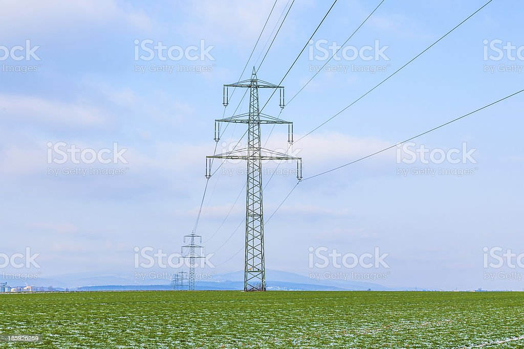 fields with snow in winter and electricity tower royalty-free stock photo