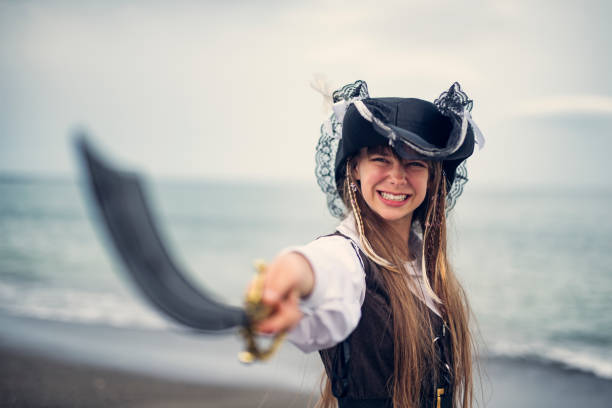fierce pirate girl holding a sabre - pirates stock photos and pictures
