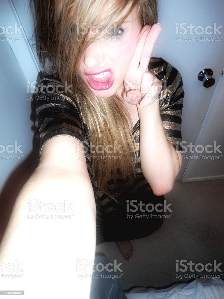 Fierce young blonde girl takes a playful selfie stock photo