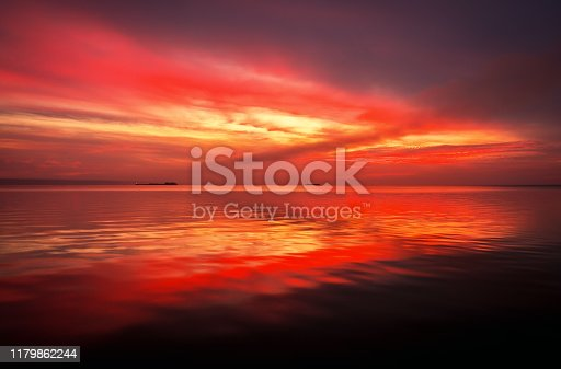 Fiery dramatic landscape with the sea, beautiful sky and ships. Dawn. small waves, almost calm.