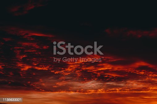 Fiery red blood vampire dawn. Amazing warm dramatic fire cloudy sky. Vivid orange sunlight. Atmospheric background of sunrise in overcast weather. Hard cloudiness. Storm clouds warning. Copy space.