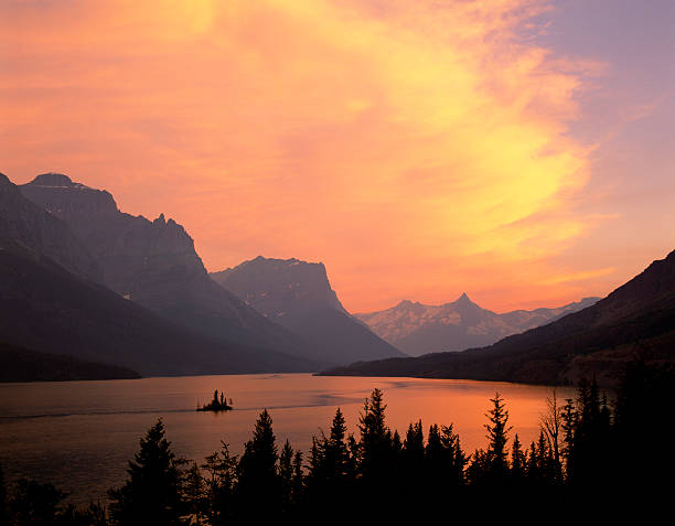 fiery sky over st. mary lake - st. mary lake stock pictures, royalty-free photos & images